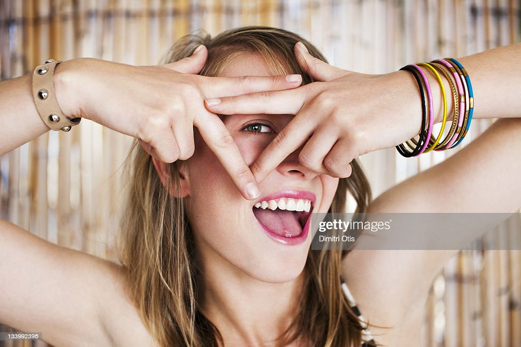 Woman looks through triangle made with her fingers : Stock Photo