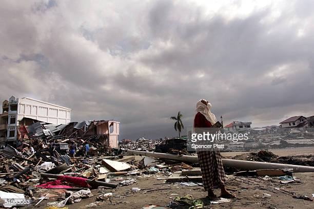 Woman looks up at the sky while waiting for a relative outside of her destroyed home January 14, 2005 in Banda Aceh, Indonesia. Citing safety...