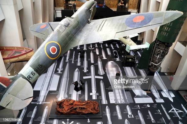 A woman looks up at The Supermarine Spitfire as Ai Weiwei's History Of Bombs is unveiled at the reopening of the Imperial War Museum on July 29 2020...