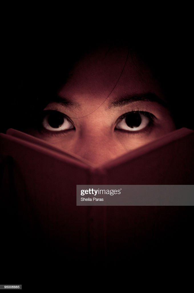 Woman looks up from reading : Stock Photo