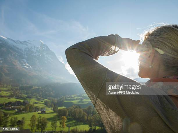 Woman looks up to Eiger North Face and pastures