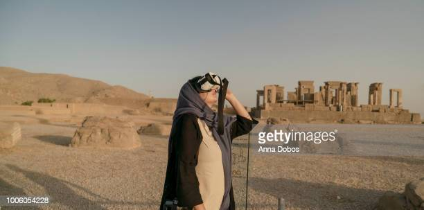 Woman looks up using a VR device with ruins of Persepolis behind
