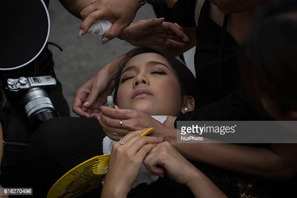 A woman lose consciousness due to the heat as mourners perform the Royal Anthem at Sanam Luang in Bangkok Thailand on October 22 2016 More than...