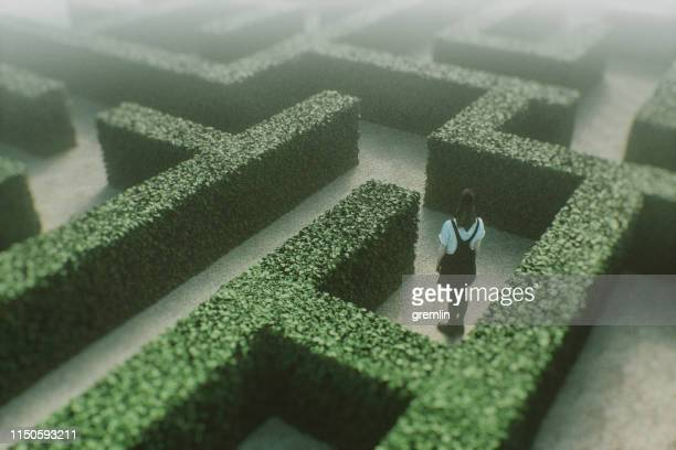 woman lost in park maze - lost stock pictures, royalty-free photos & images