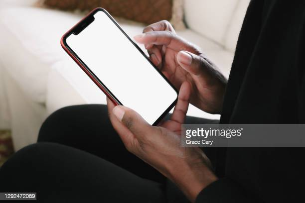 woman lounges on sofa with smart phone - hand stock pictures, royalty-free photos & images