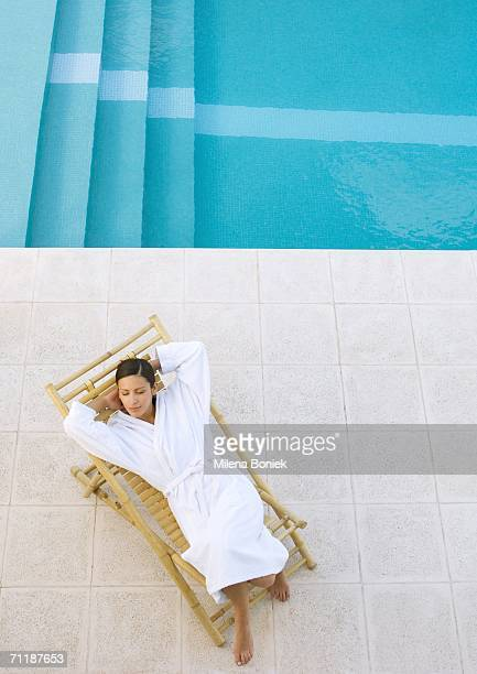 Woman lounging in chair by pool, high angle view