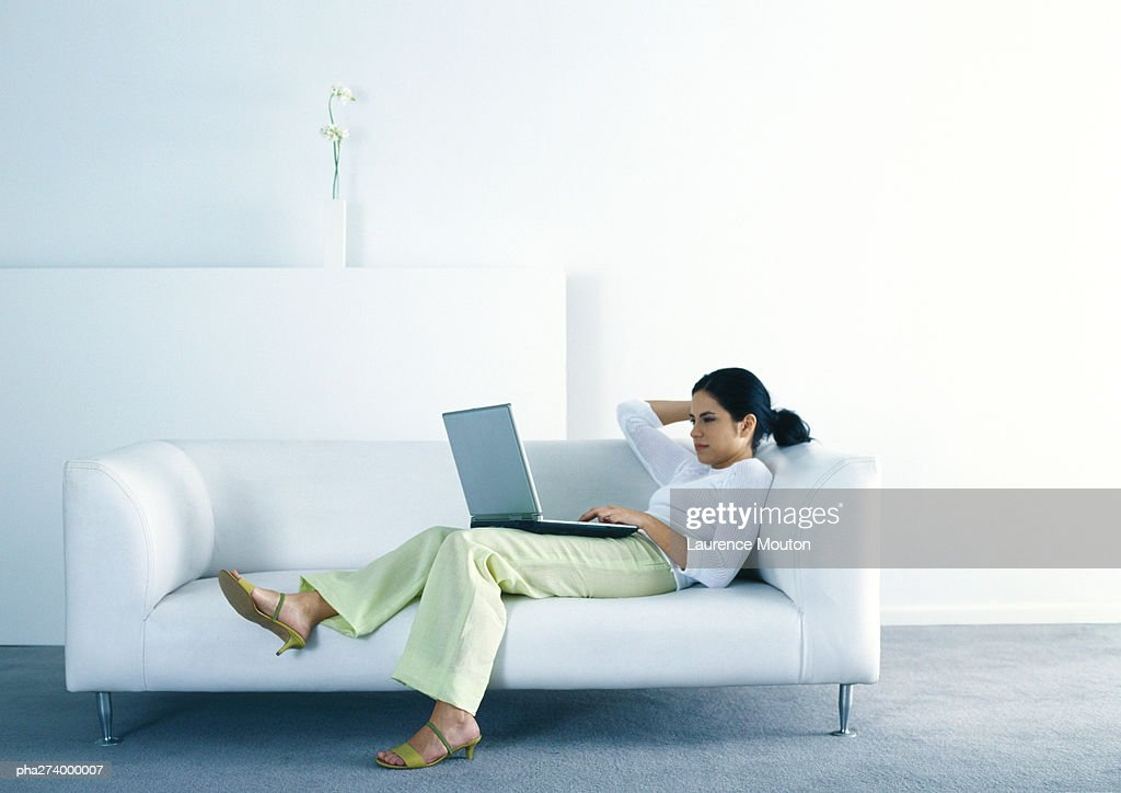 Woman lounging on sofa and using laptop : Stockfoto