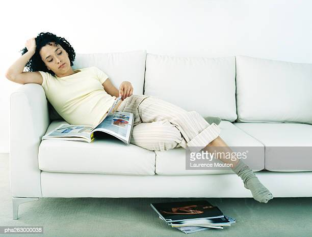 Woman lounging on sofa looking at magazine with stack of magazines on floor, full length