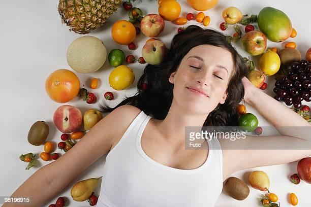 Woman lying among fruit