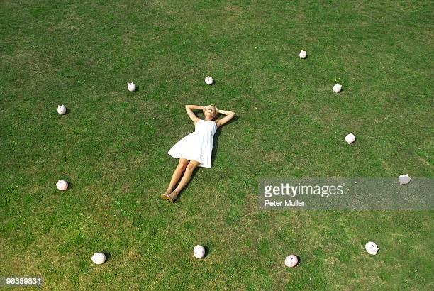 woman lying amongst piggy banks