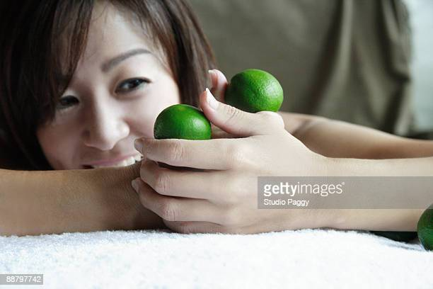 Woman lying and holding two lemons