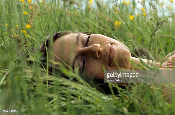 woman lying and sleeping in meadow - one young woman only stock pictures, royalty-free photos & images