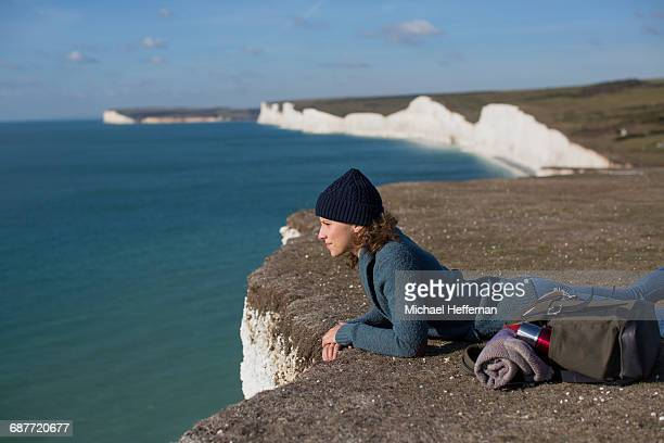 Woman lying at edge of cliff
