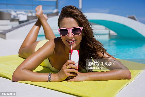Woman lying at the poolside drinking