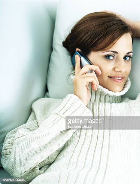 woman lying back on pillow, holding cell phone to ear, smiling at camera - turtleneck stock pictures, royalty-free photos & images
