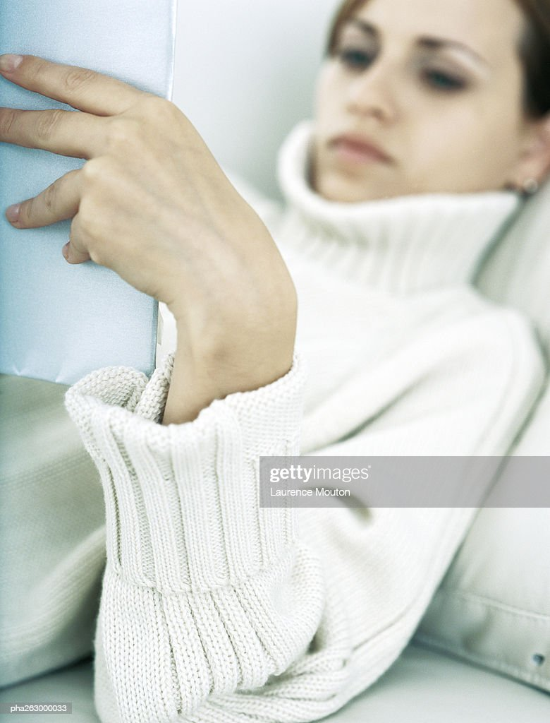 Woman lying back on pillow holding up book : Stockfoto