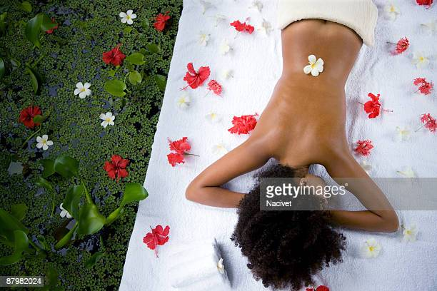 Woman lying by pond with flower around her at spa