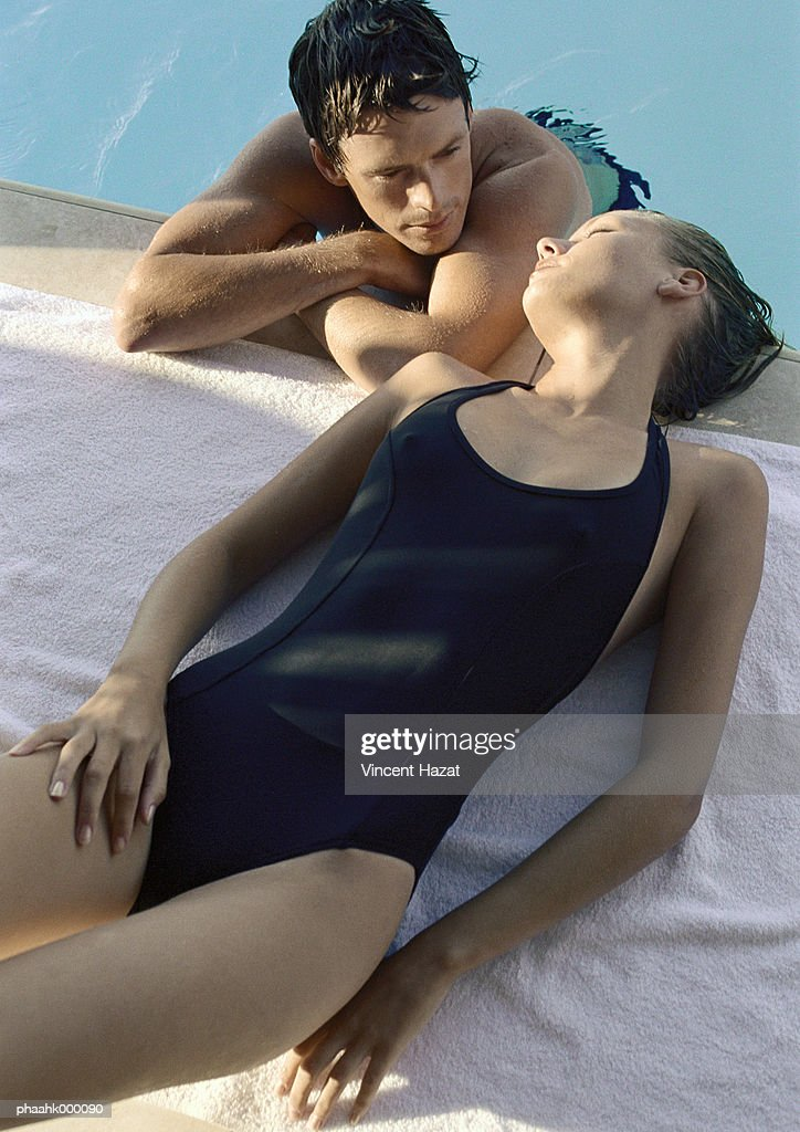 Woman lying by pool, man in pool leaning on edge of pool : Stockfoto