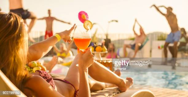 mujer tumbada junto a piscina con cóctel en la mano mientras la otra danza de la gente en y alrededor de la piscina al atardecer - pool party fotografías e imágenes de stock