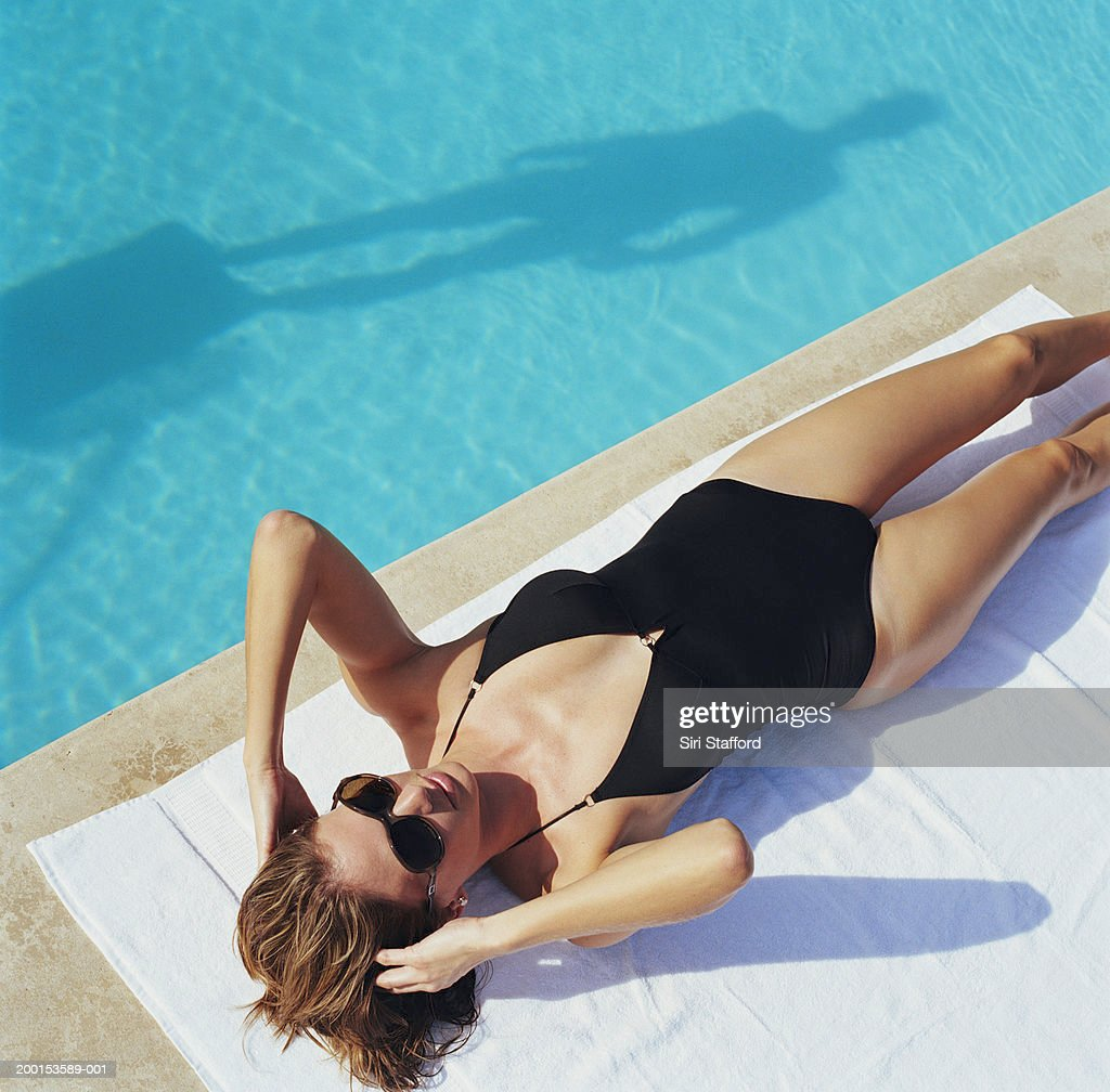 Woman lying by side of pool, elevated view : Foto stock