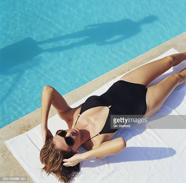 woman lying by side of pool, elevated view - one piece swimsuit stock pictures, royalty-free photos & images