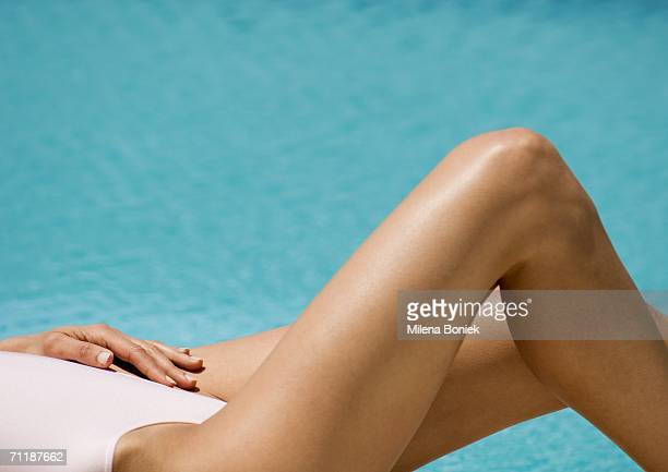 Woman lying by side of pool, partial view