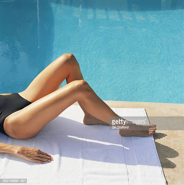 Woman lying by side of pool (low section)