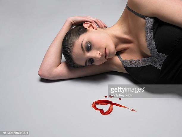 Woman lying dead on floor by heart shape drawn by blood