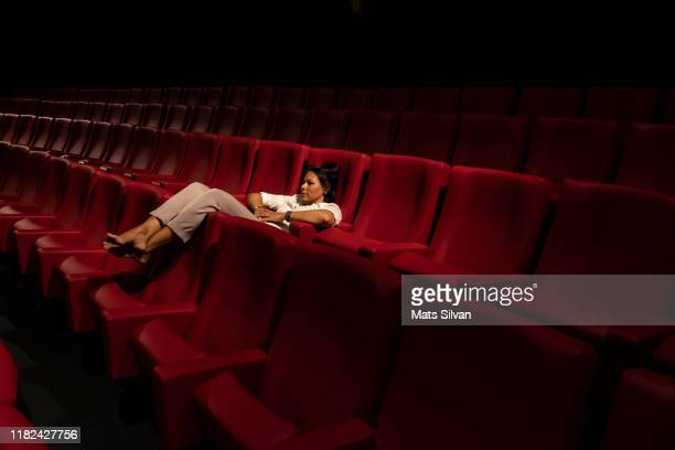 woman lying down alone in a movie theater - filmvorführung stock-fotos und bilder