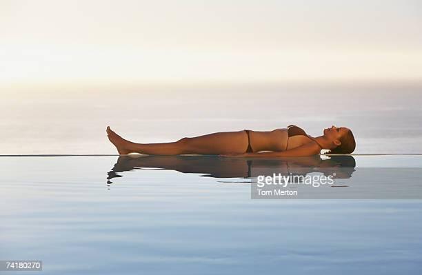 frau liegen im bikini am rand des infinity-pool - lying down stock-fotos und bilder