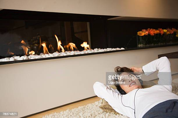 woman lying down in front of fireplace - hitech mod a stock pictures, royalty-free photos & images