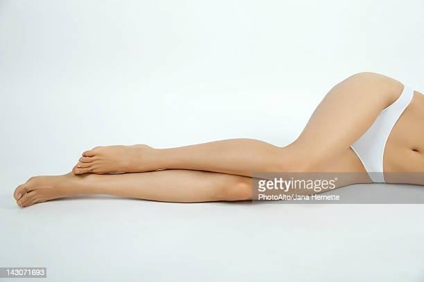 Woman lying down in underwear, low section