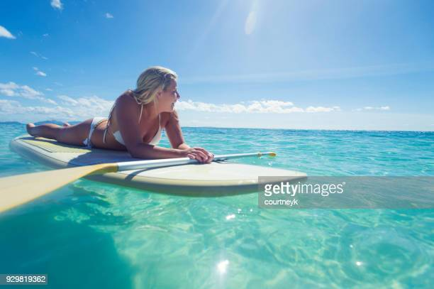 Woman lying down on a stand up paddleboard.