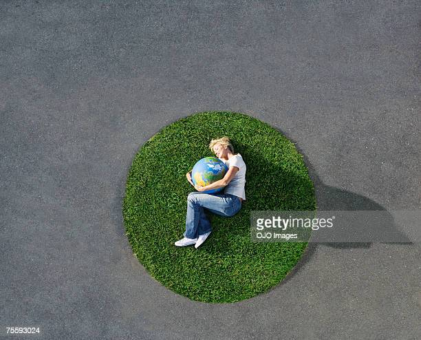 woman lying down on circle of grass on pavement with globe - world kindness day stock photos and pictures