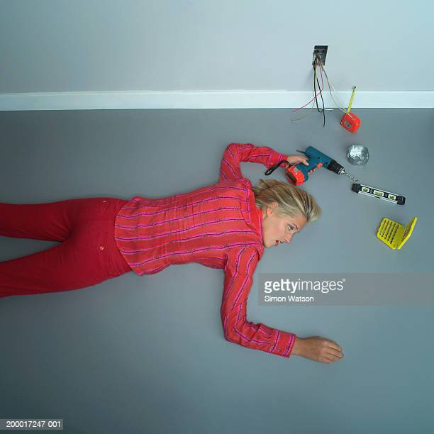 Woman  lying down on floor, with home tools holding power drill.