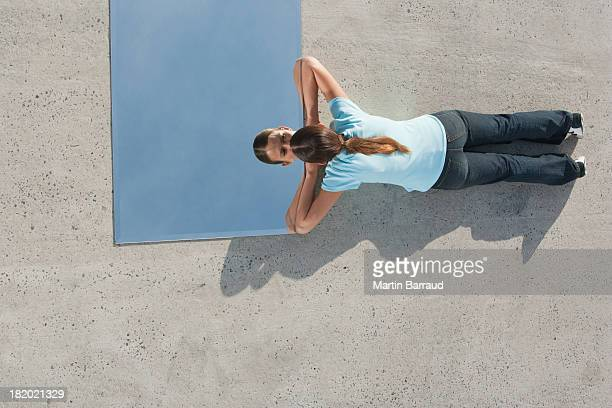Woman lying down on ground with mirror and reflection