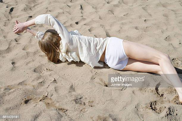 Woman lying down on sand