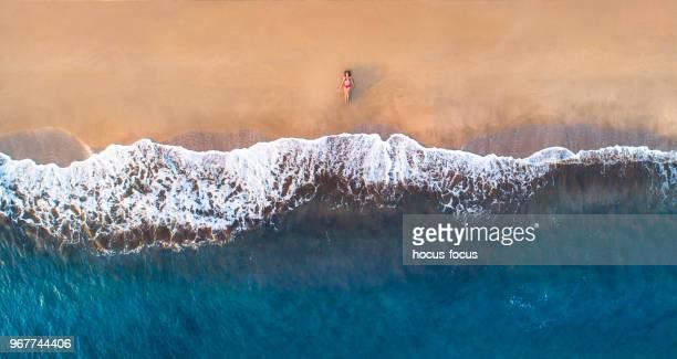 Frau im liegen am Sandstrand im Sommer