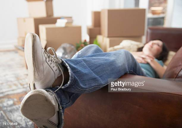 Woman lying down on sofa in home with cardboard boxes