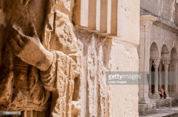 Woman lying down on stone ledge in church in Arles in France.