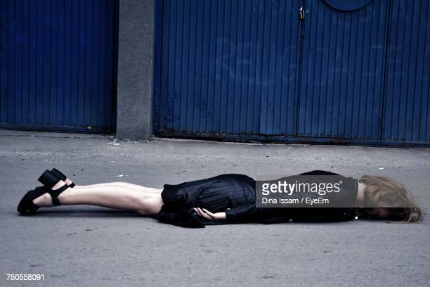woman lying down on street - binge drinking stock photos and pictures