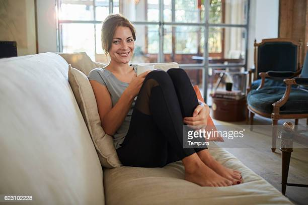 woman lying down on the sofa and enjoying coffee. - yoga pants stock photos and pictures