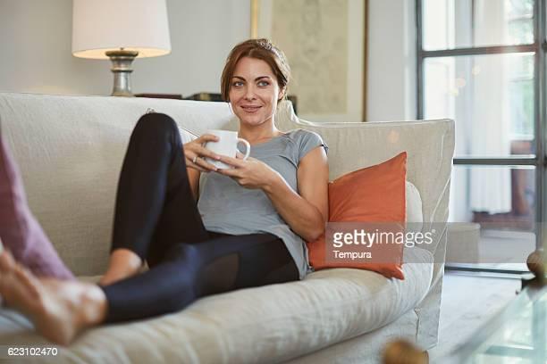 woman lying down on the sofa and enjoying tea. - yoga pants stock photos and pictures