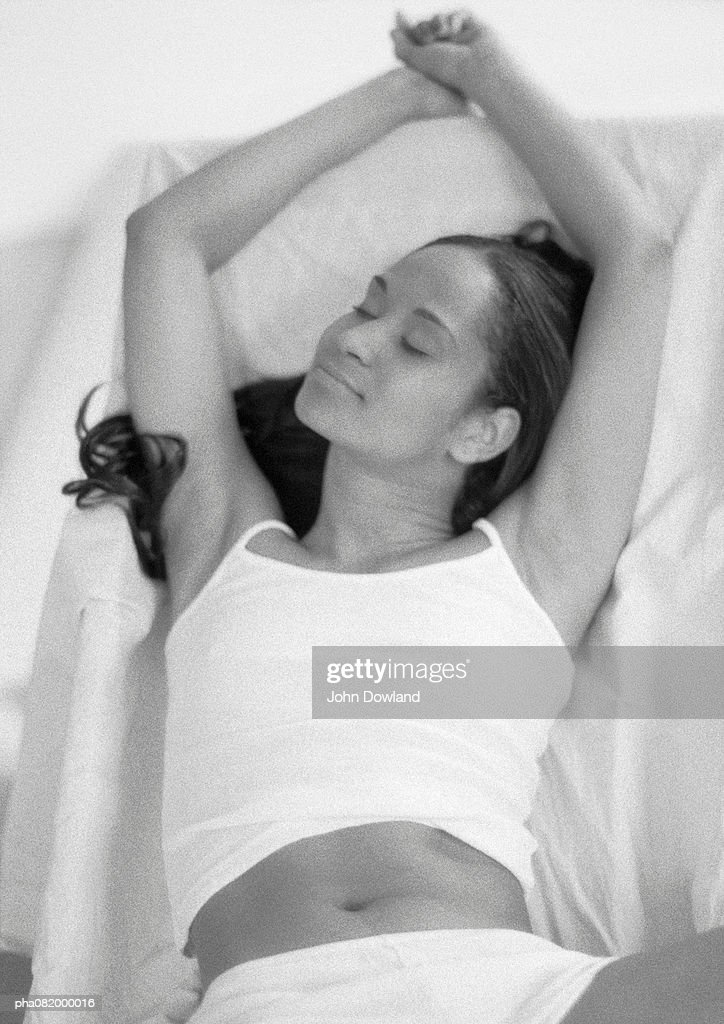 Woman lying down stretching arms up, B&W. : Stock Photo