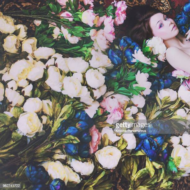 a woman lying down surrounded by flowers. - kristina rose fotografías e imágenes de stock