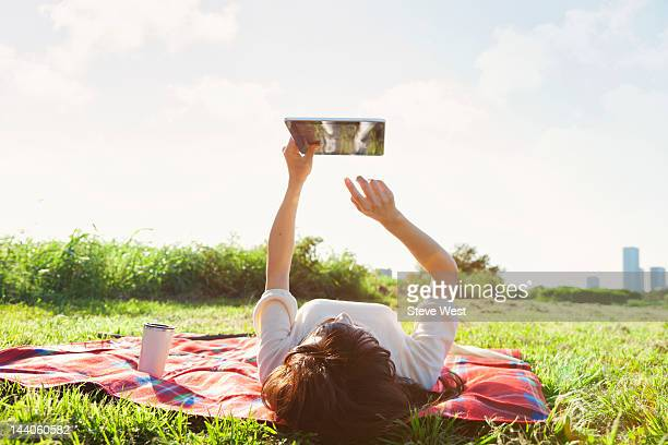 Woman lying down using digital tablet