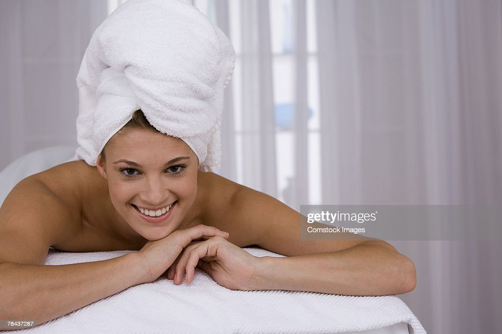 Woman lying down with a towel on her head : Stockfoto
