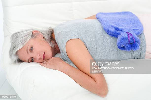 Woman lying down with hot water bottle