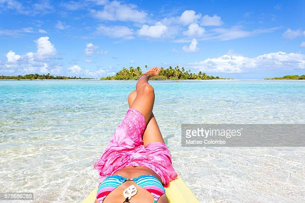 Woman lying down with legs crossed in the blue sea