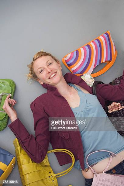 woman lying down with purses - lying down stock-fotos und bilder